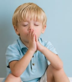 Preschool aged boy praying.