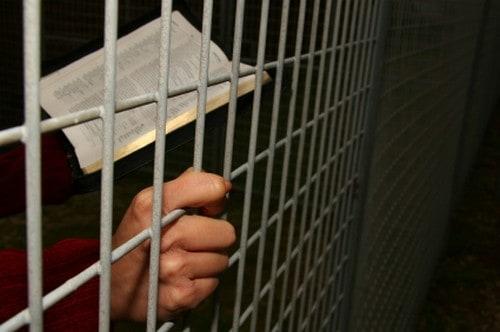 Bible and praying hands behind bars