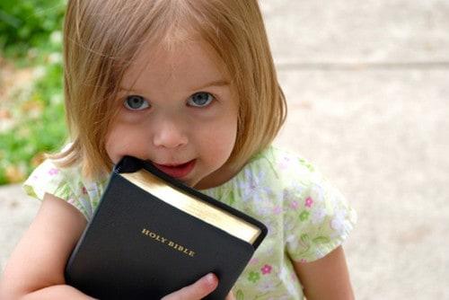 Little girl holding Bible